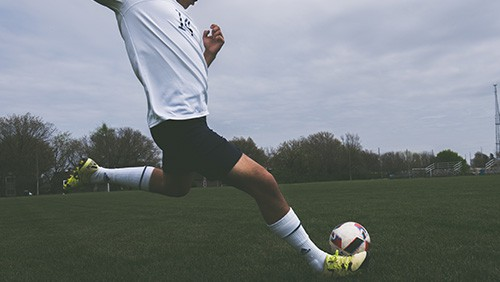 Soccer player approaching to kick the ball